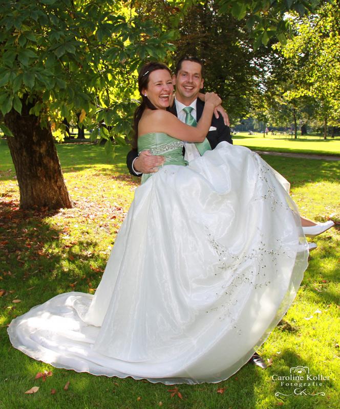 bräutigam trägt braut im park