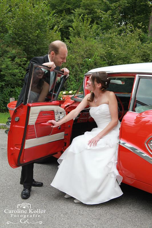 Braut sitzt im roten Oldtimer