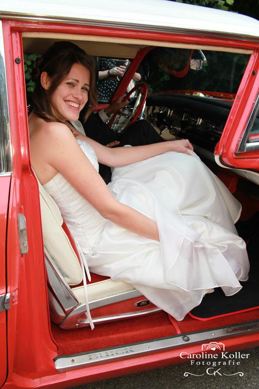 Glückliche Braut im roten Oldtimer